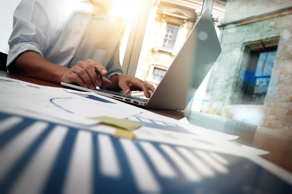 business documents on office table with smart phone and digital tablet and graph financial diagram and man working in the background.jpeg